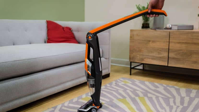 Person using a cordless vacuum cleaner to clean carpet