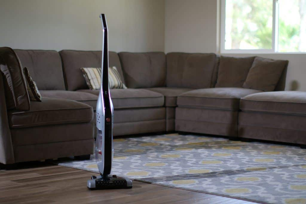 A Hoover stick vac sits in a living room with both a rug and bare floor
