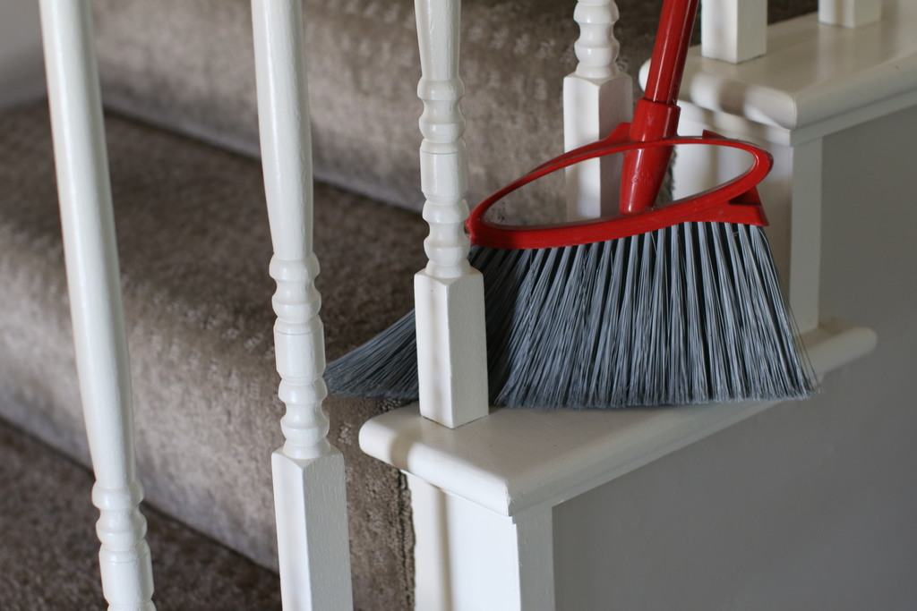 using broom to sweep carpeted stairs