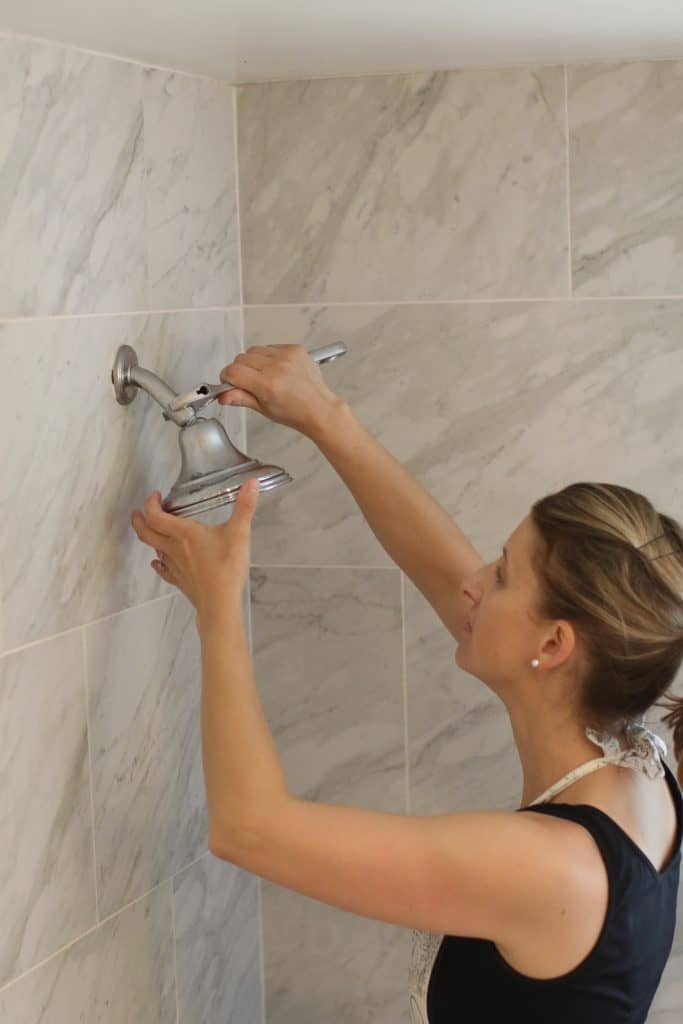 A woman unscrews a shower head from the wall pipe
