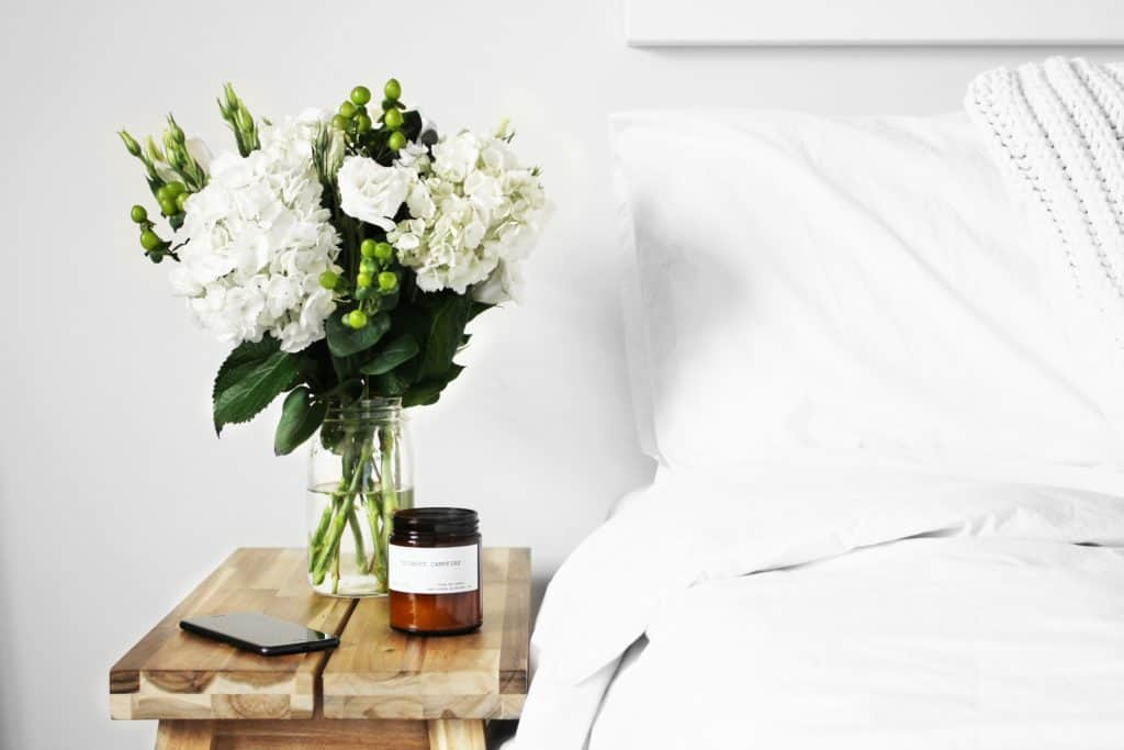 White flowers in a vase on top of a table beside a white bed