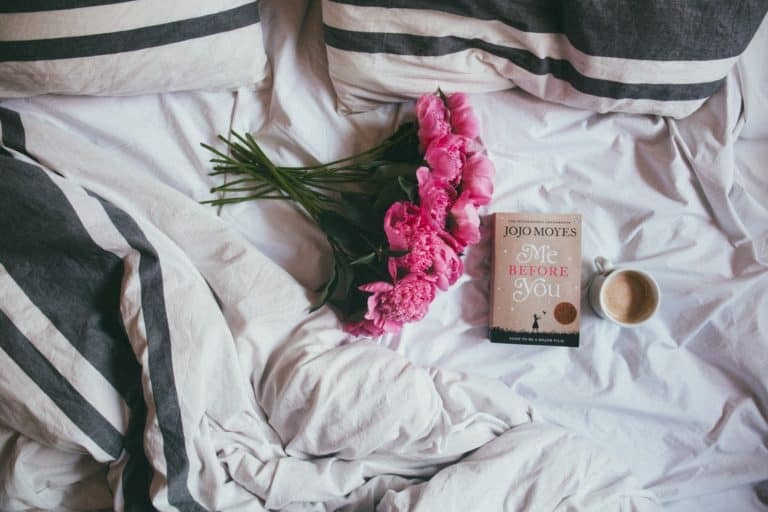 pink roses and a book with a cup of coffee sitting on top of a bed