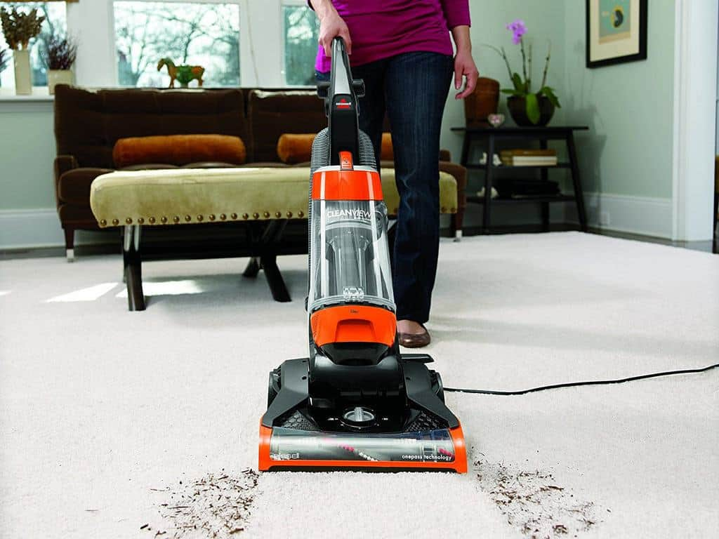 A woman in a maroon long sleeved top using an Orange Bissel Clean View Vacuum cleaner to clean off dust and dander from carpet