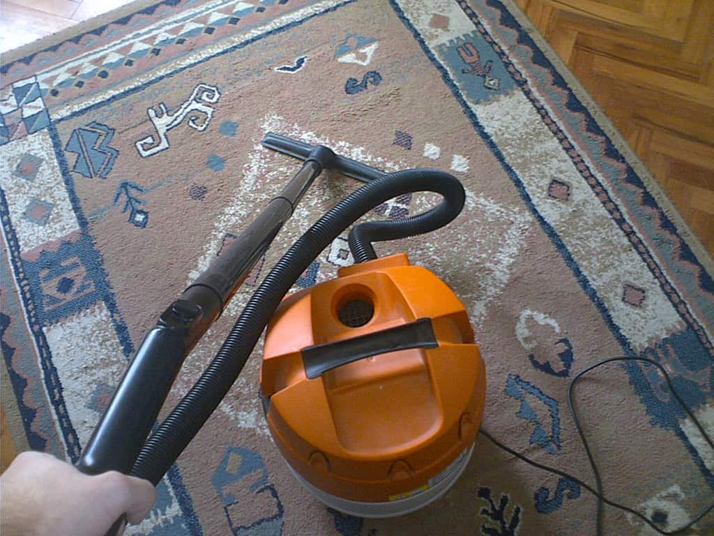 Round orange vacuum cleaner used to clean a dirty brown area rug
