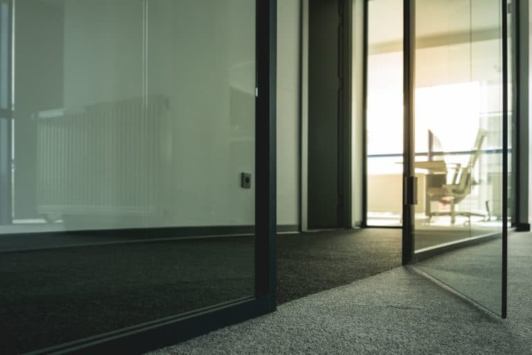Gray carpet and transparent glass doors by a hallway