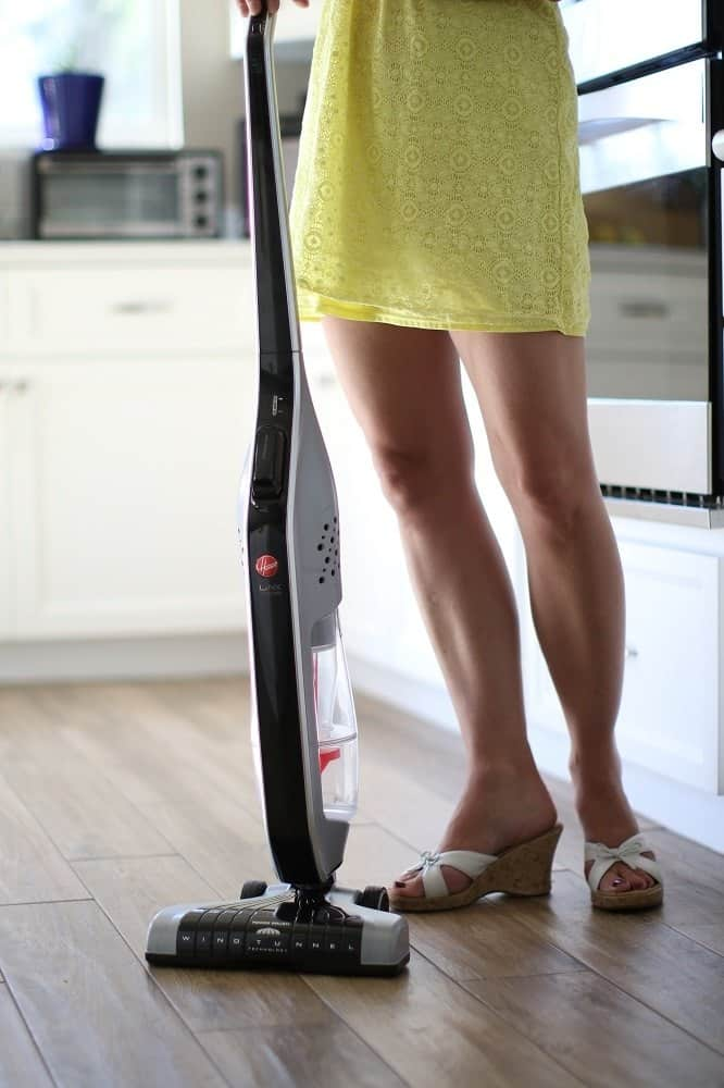 An attractive women standing in a kitchen holding a Hoover stick vacuum for cleaning.