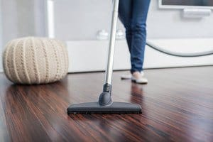 Vacuum cleaner being swept across a hardwood foor surface, beige poof ottoman is beside it
