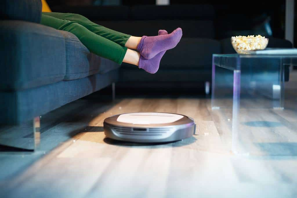Young girl with green pants and purple socks lifts feet to make way for robotic vacuum cleaner