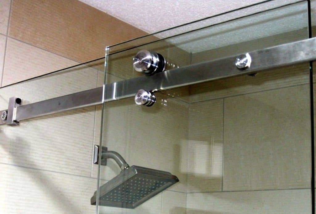 Glass sliding door with tracks and hinges by a shower head