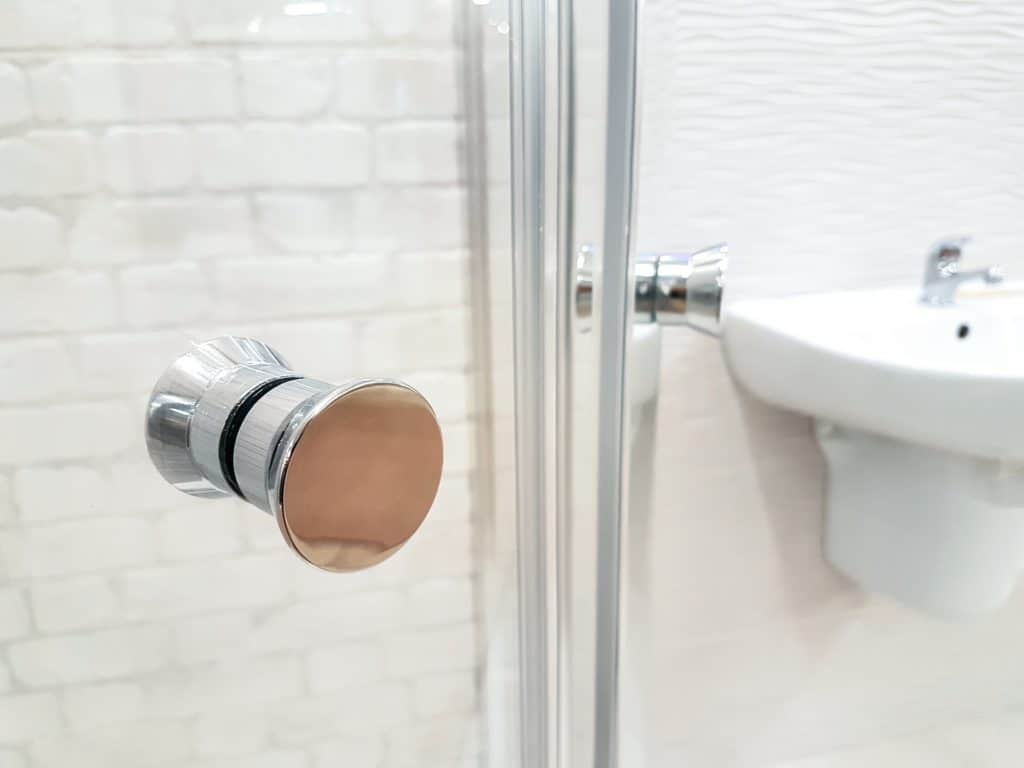 Glass doors with a silver knob in a white tiled bathroom