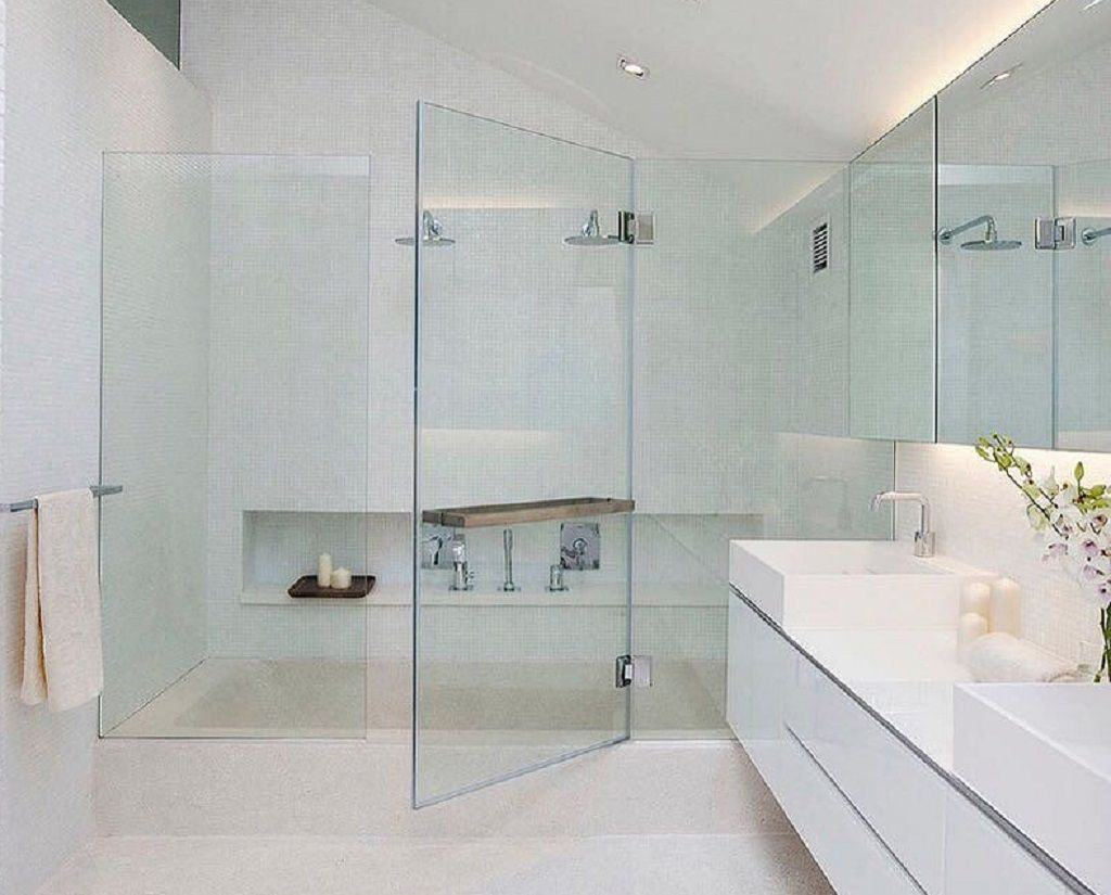 Frameless glass shower doors in a white luxurious bathroom