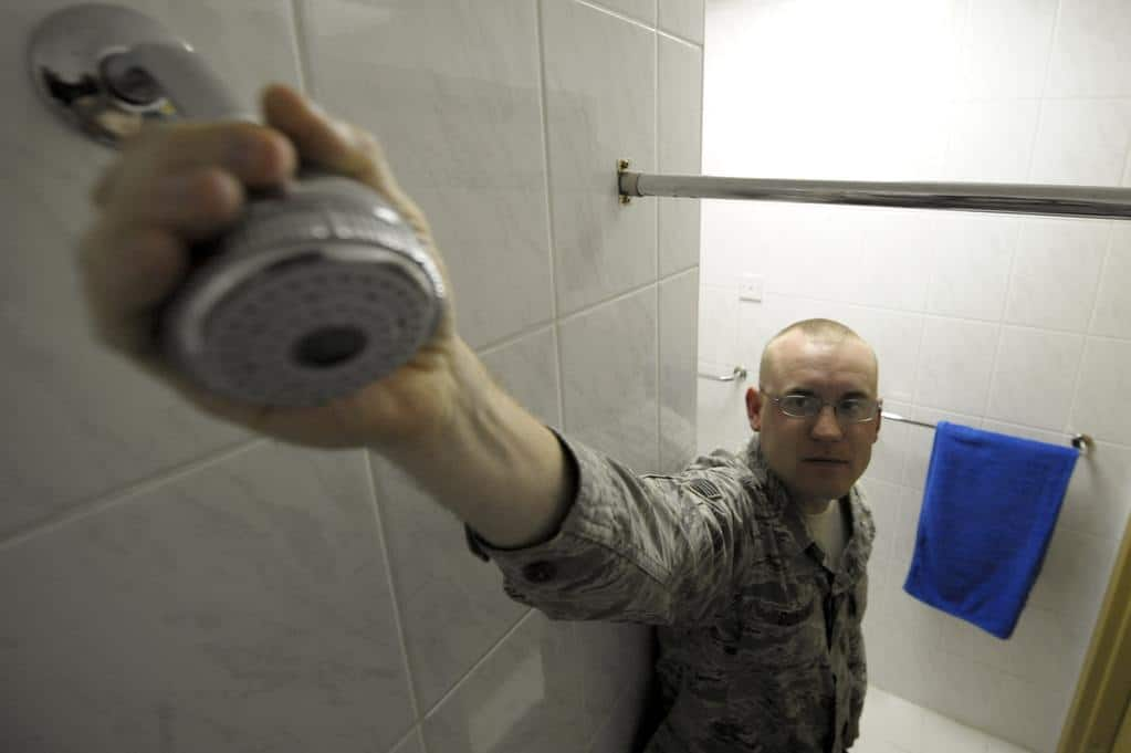 Man reaching out to his bathroom shower head