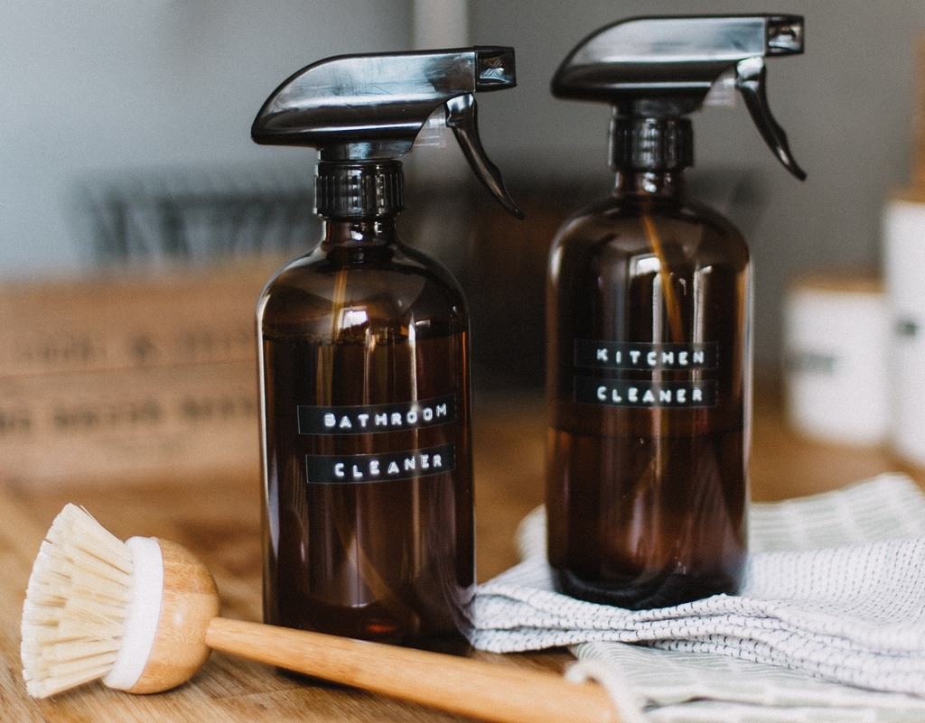 A mini wooden brush and two black spray bottles labeled bathroom cleaners, with one sitting on top of a gray towel on a wooden counter top