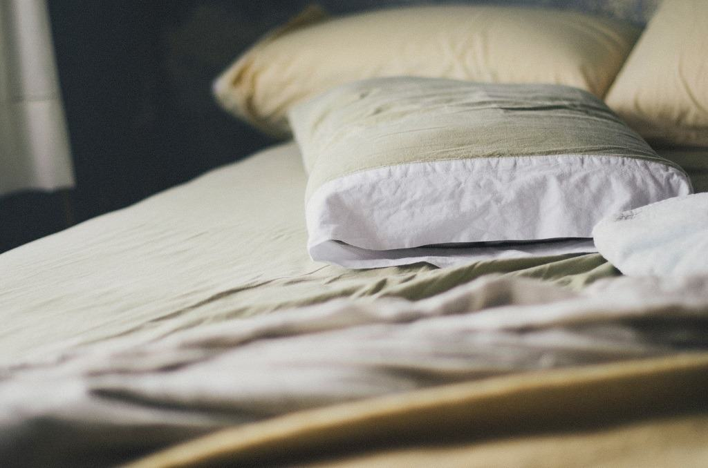 Gray pillows and folded sheets on a bed