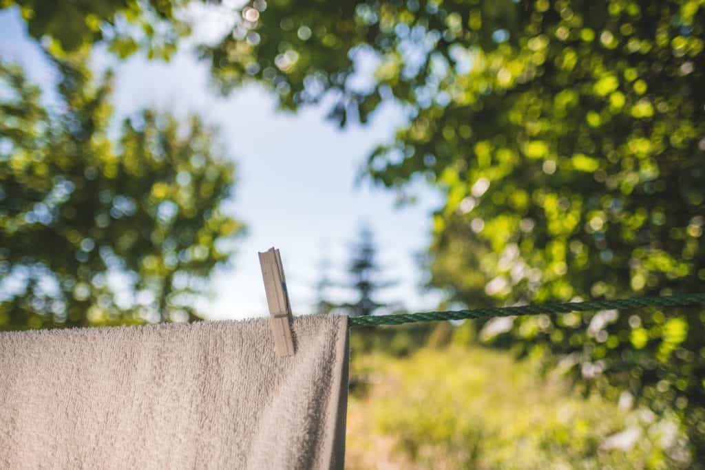 A white soft blanket hanging outdoors on a clothesline