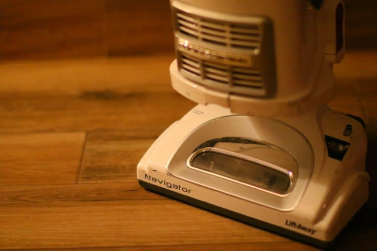 Shark Navigator vacuum cleaner sitting on hardwood floor