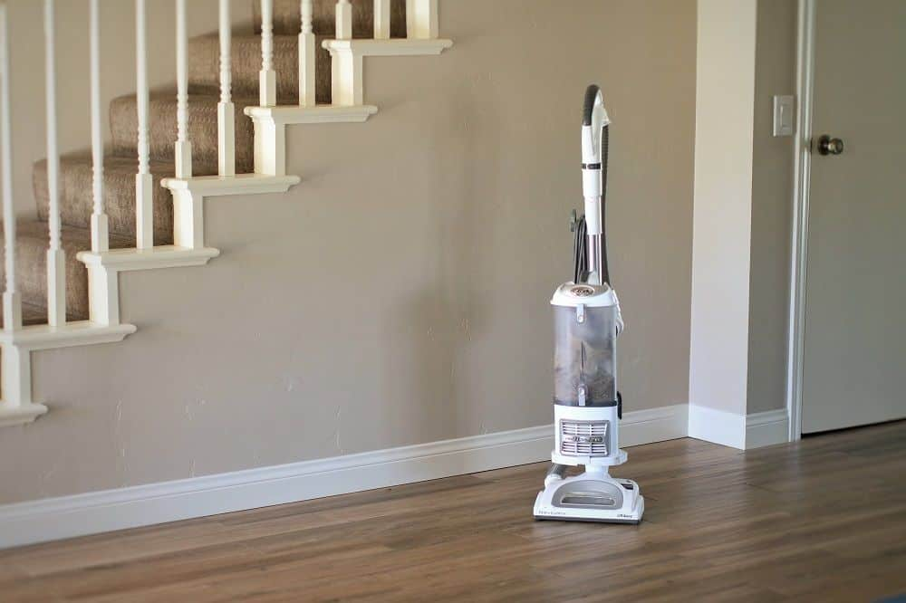 The Shark Navigator corded stick vacuum sits upright on hardwood flooring