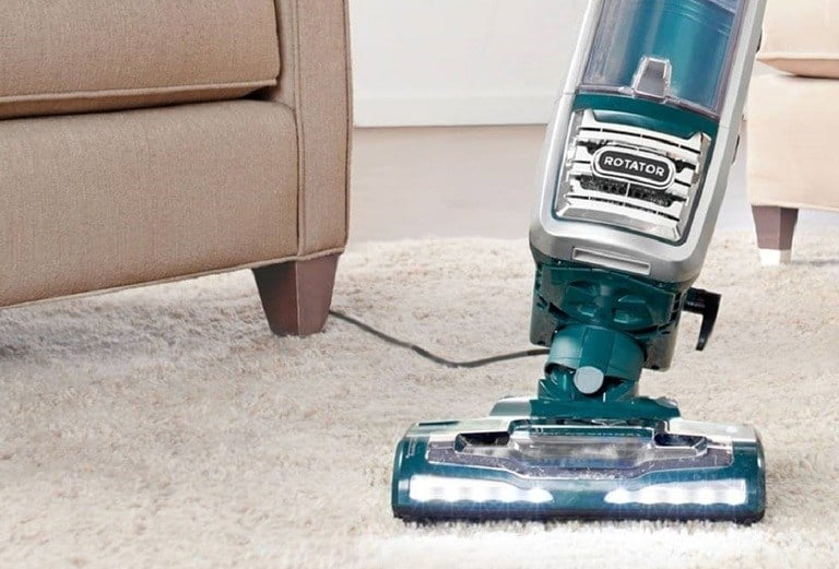 Blue Shark Rotator Vacuum with lit up LED lights is swept around light beige carpets by a tan sofa