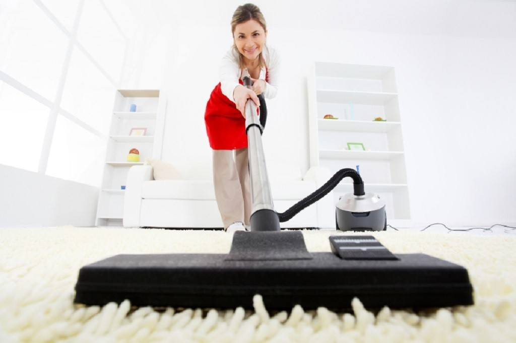 Cleaning lady vacuuming a soft white carpet in living room
