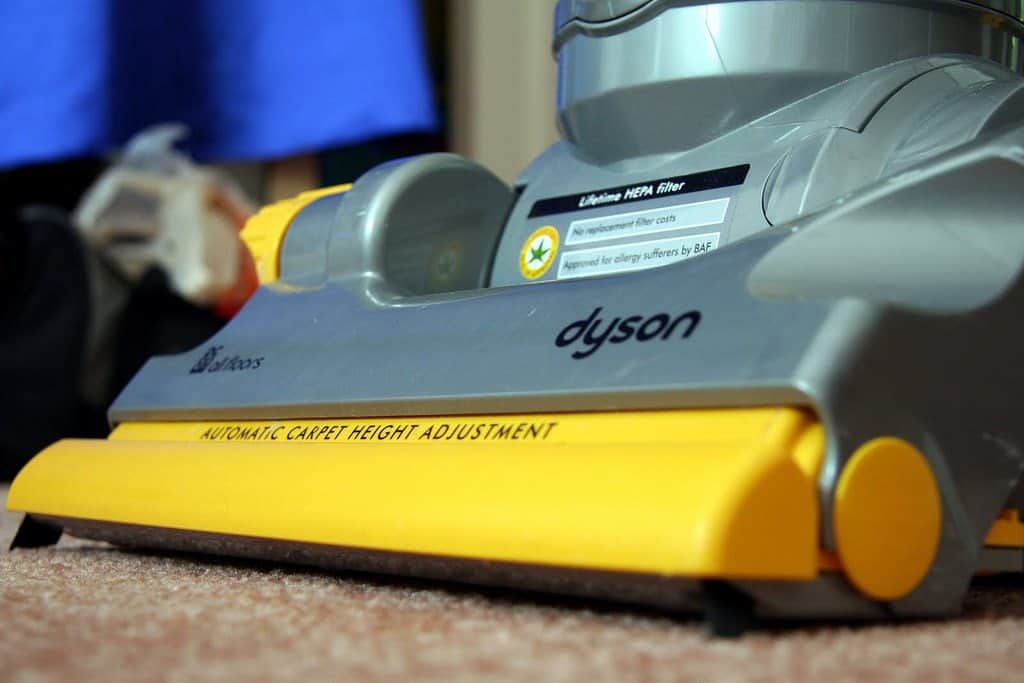 Up-close yellow and gray Dyson vacuum cleaner on carpet