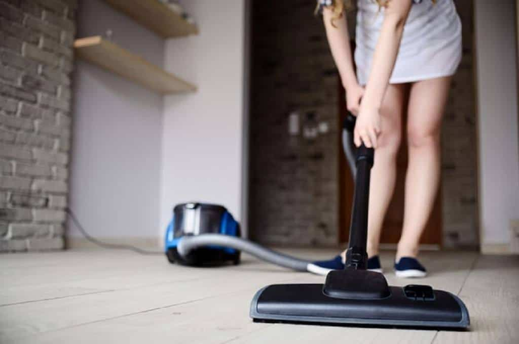 Woman in a beige dress using a Black Shark Vacuum to clean her hardwood floors
