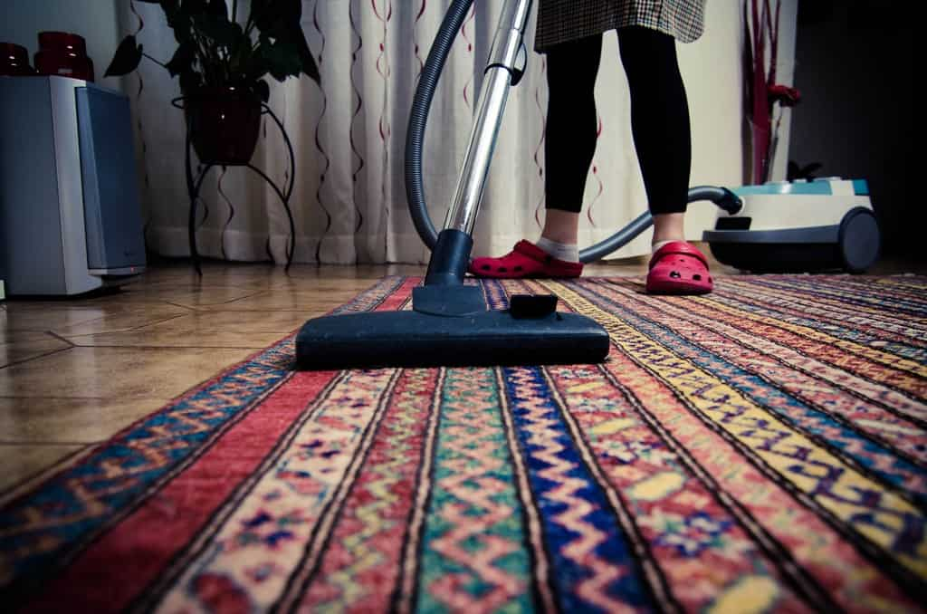 Woman vacuuming a colorful area rug