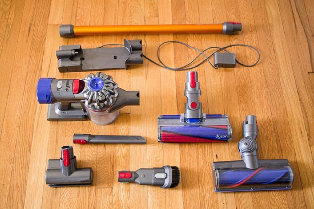Dyson Stick Vacuum disassembled and laid on a hardwood floor surface