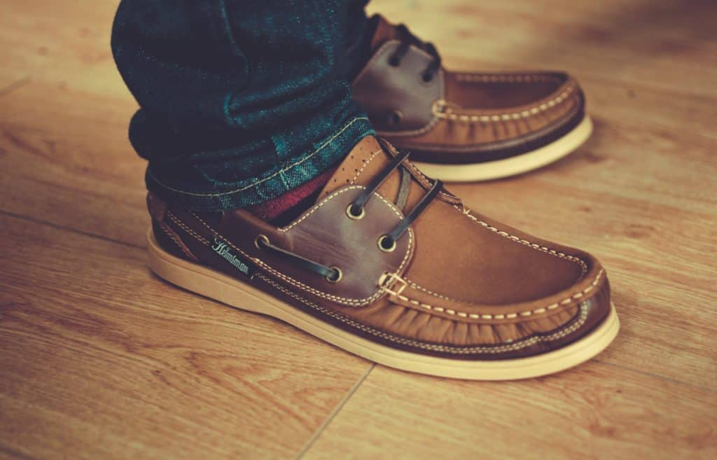 Man in brown boat shoes stands on top of light brown laminate flooring