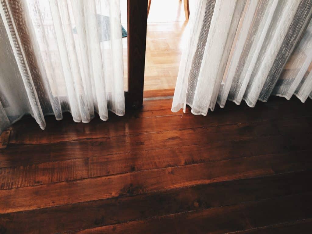 White curtains draped above glossy dark brown hardwood floors