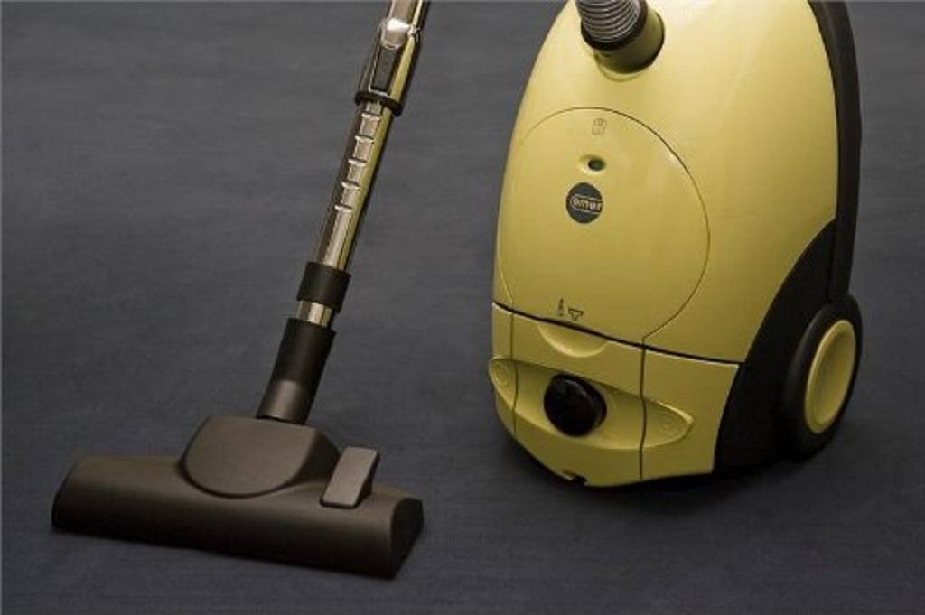 Yellow canister vacuum standing on a blue carpet
