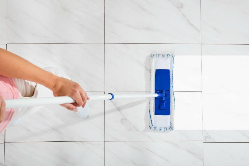 A mop is swiped on dirty white tile