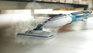 A steam mop is uesed underneath a bed