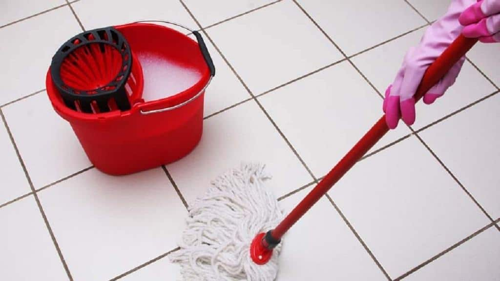 A red spin mop used on white tile floor