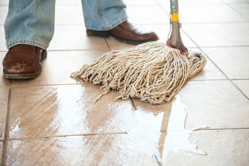 A man using a traditional mop on a wet tile floor