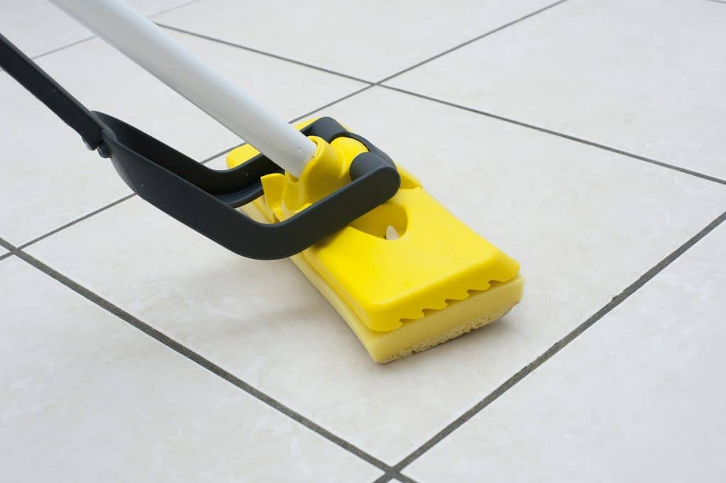 Using a yellow sponge mop on tile