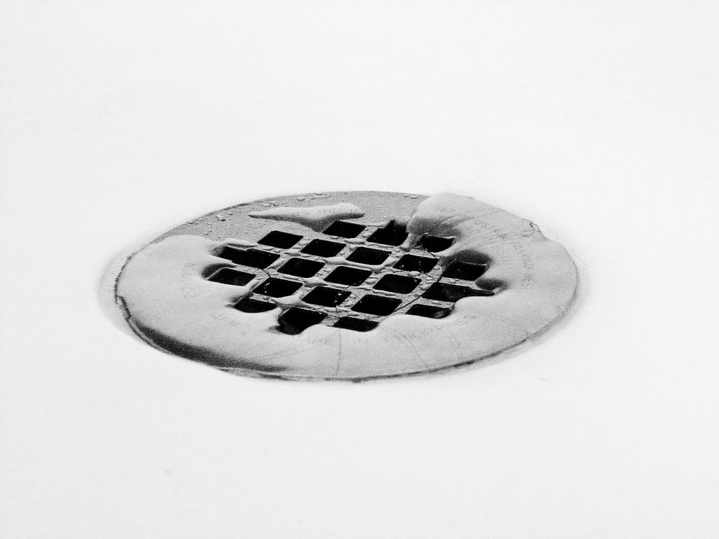 Close up of a silver shower drain trap with a few strands of hair