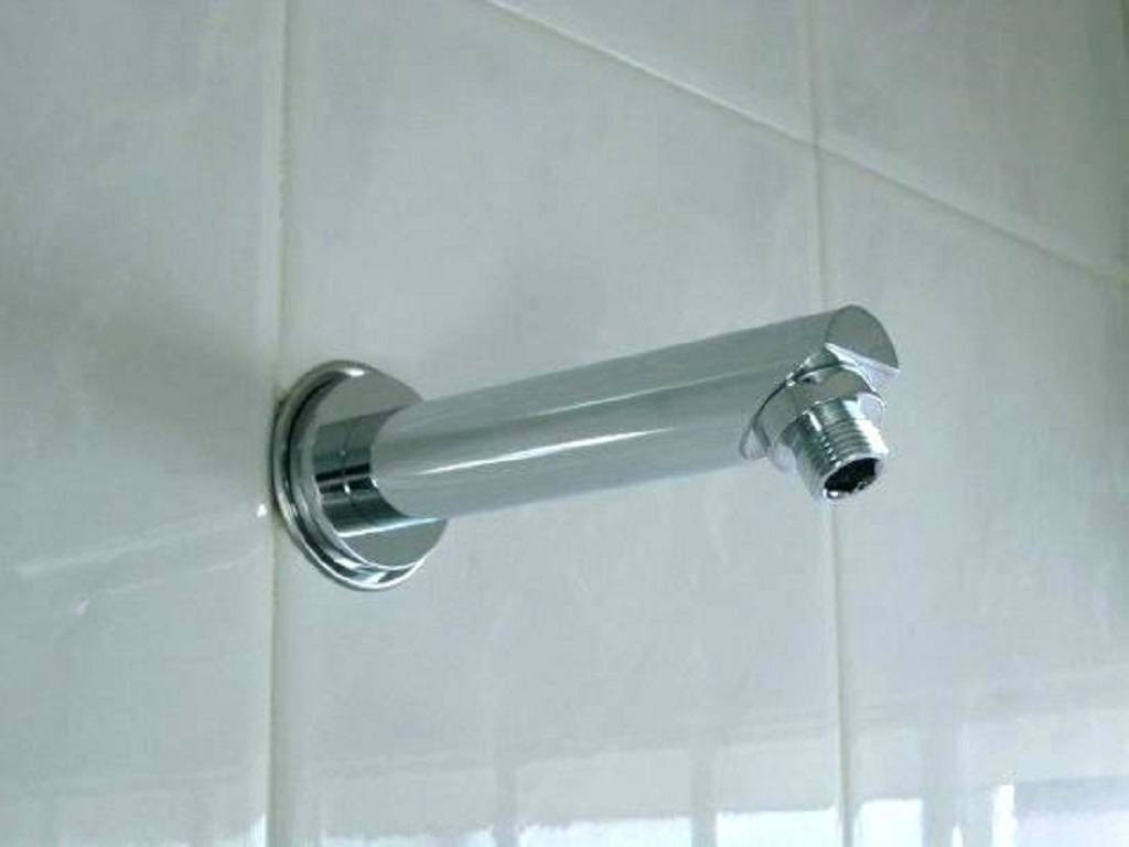 Shower arm without shower head on a tiled bathroom wall