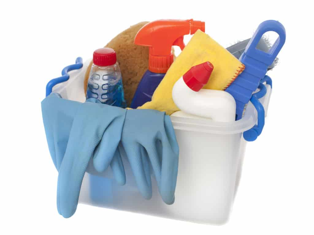 A bucket of cleaning products such as gloves, sprays, sponges, detergents and bleaches