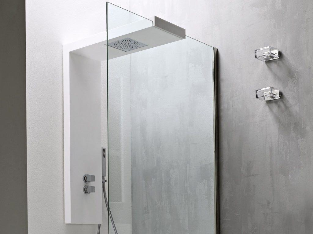 A glass shower door with a white modern shower panel