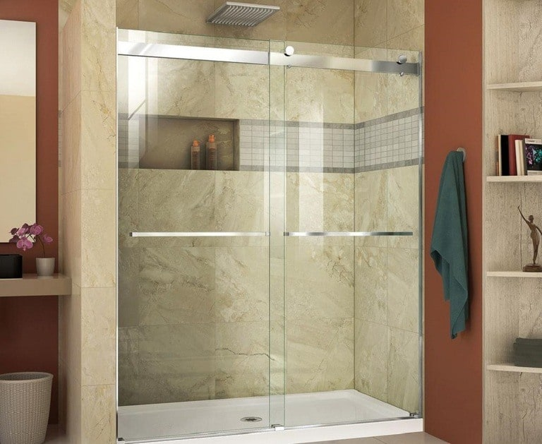 Glass shower doors in a marbled, orangey brown bathroom