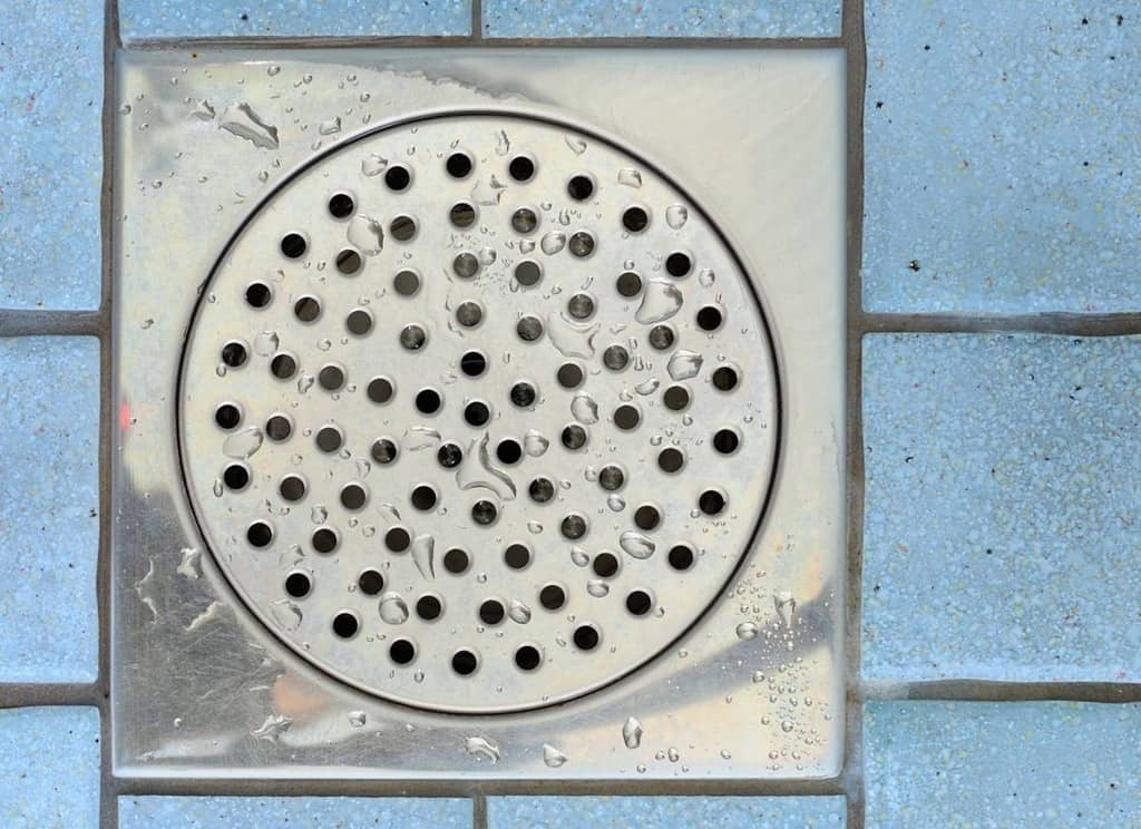 Round shower drain cover in the middle of blue square shower tiles