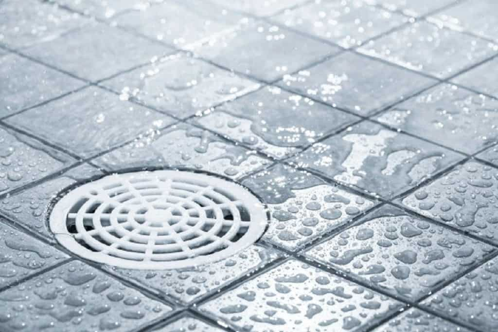 White round plastic shower drain wet from drops of water on blue square shower tiles