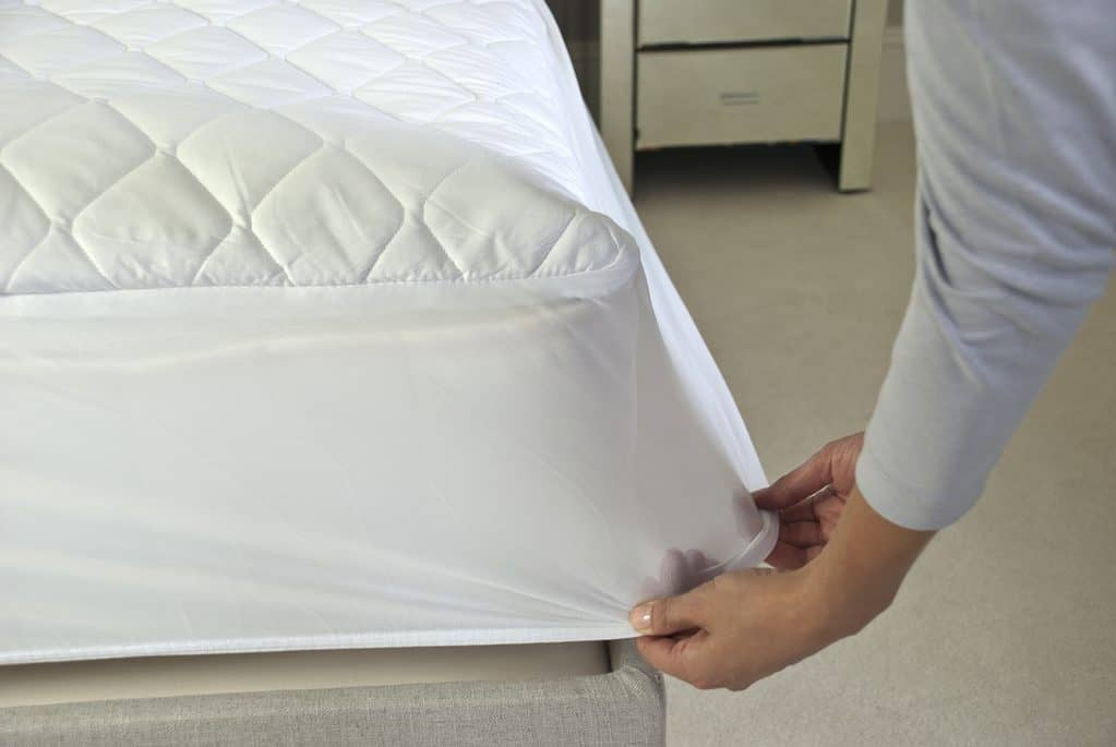 Quilted and foam based mattress cover being fitted on to a mattress