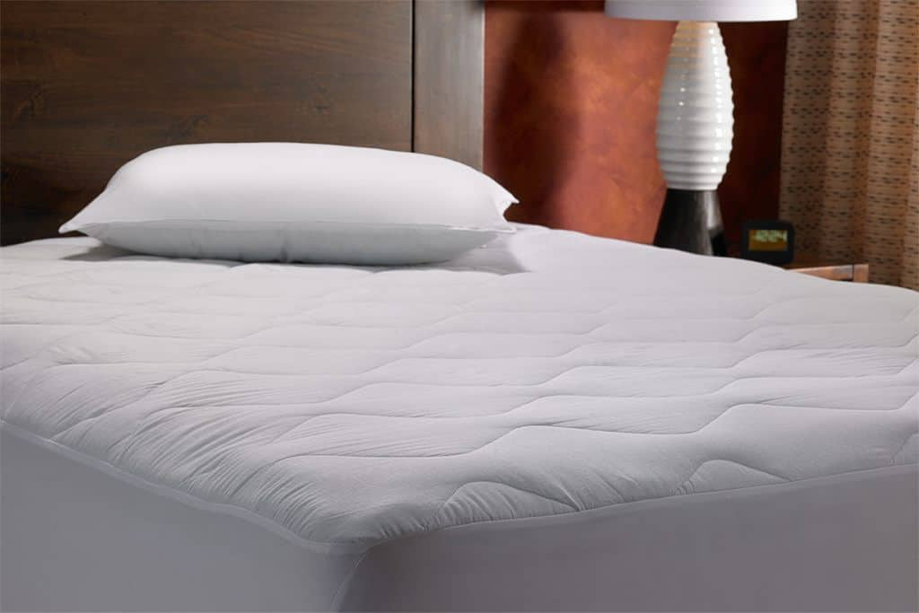 Angled view of a white mattress with a brown headboard and a white pillow
