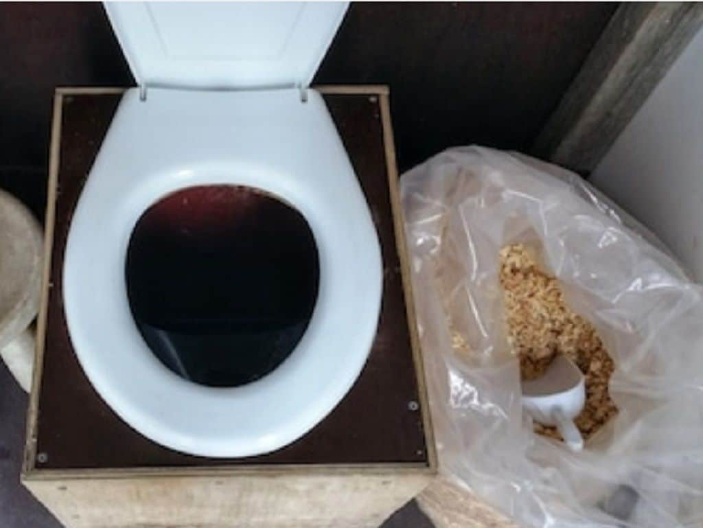 Close up of a composting toilet with a bag of filling beside it