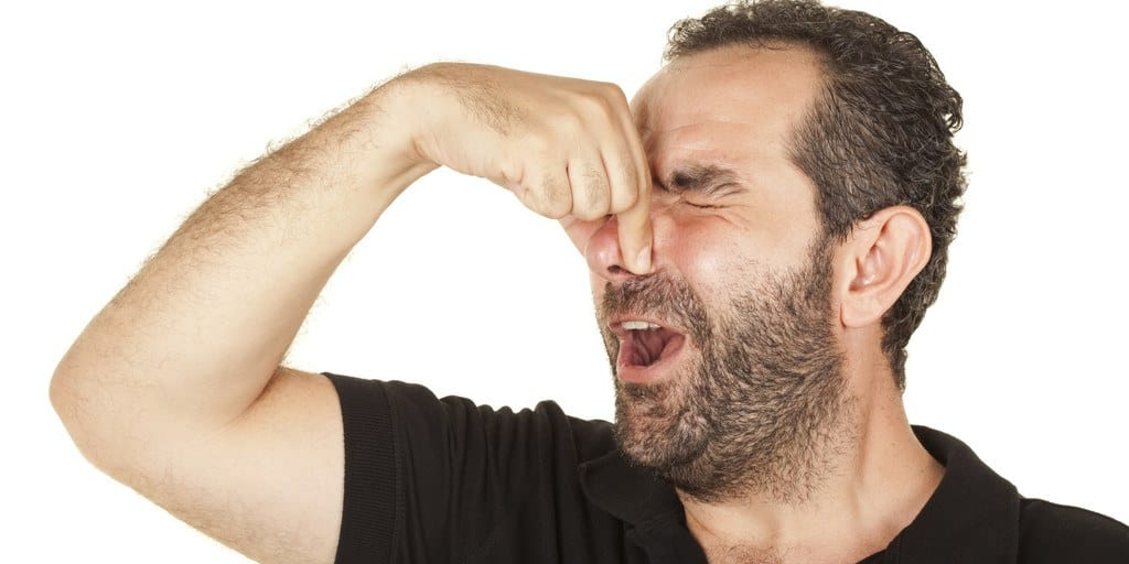 Man holding his nose because of something smelly