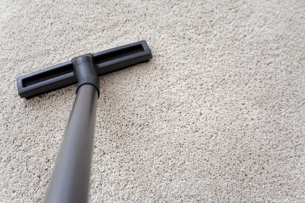 A vacuum cleaner going over berber carpet