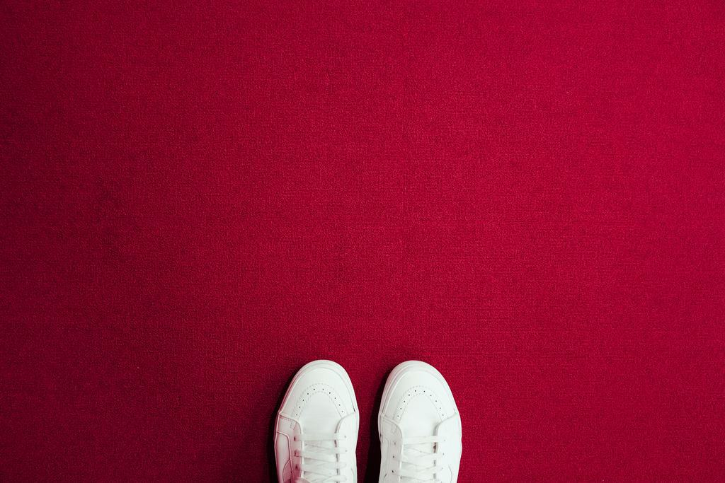 White sneakers standing on red carpet