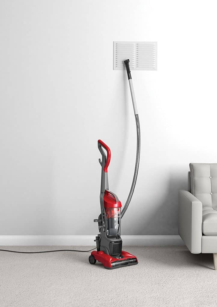 Stick vacuum red against a wall