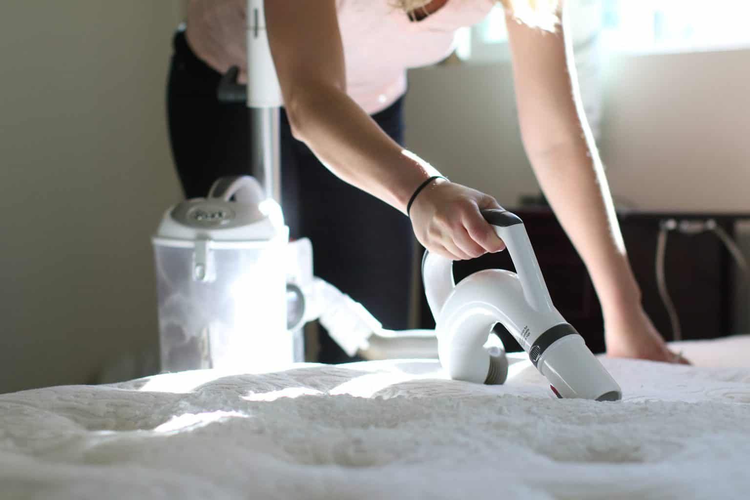A woman uses a canister vacuum to clean up baking soda off of a mattress protector